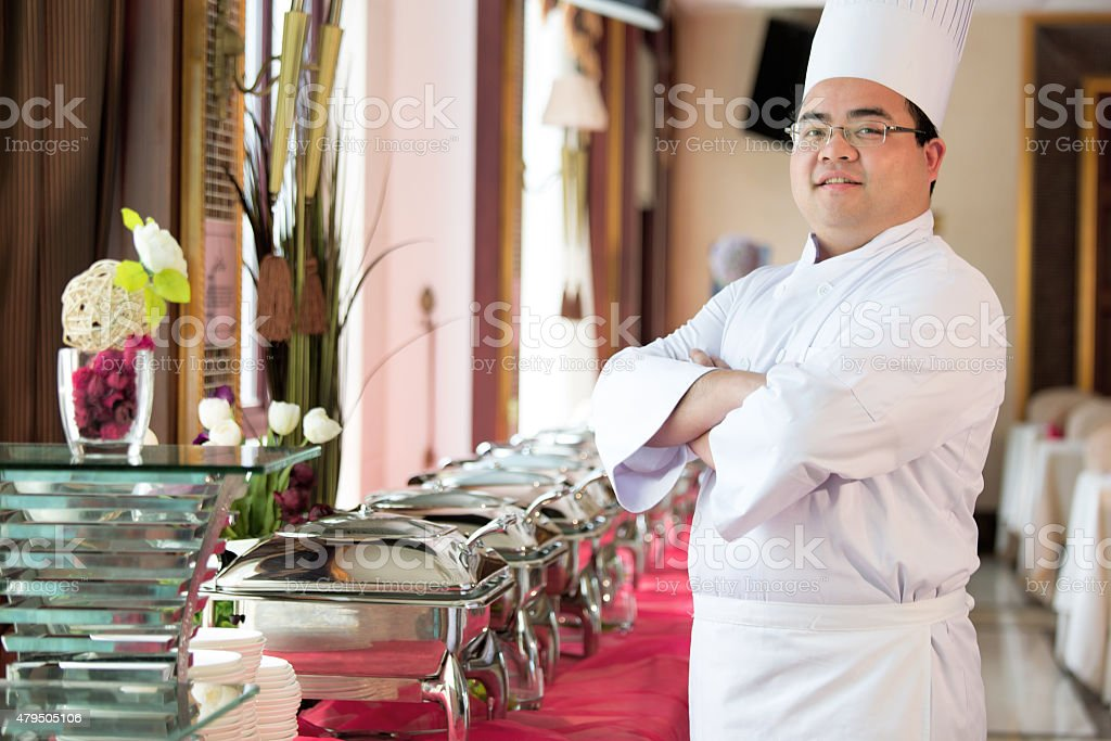 Smiling Chef In Uniform Standing Arms Crossed stock photo