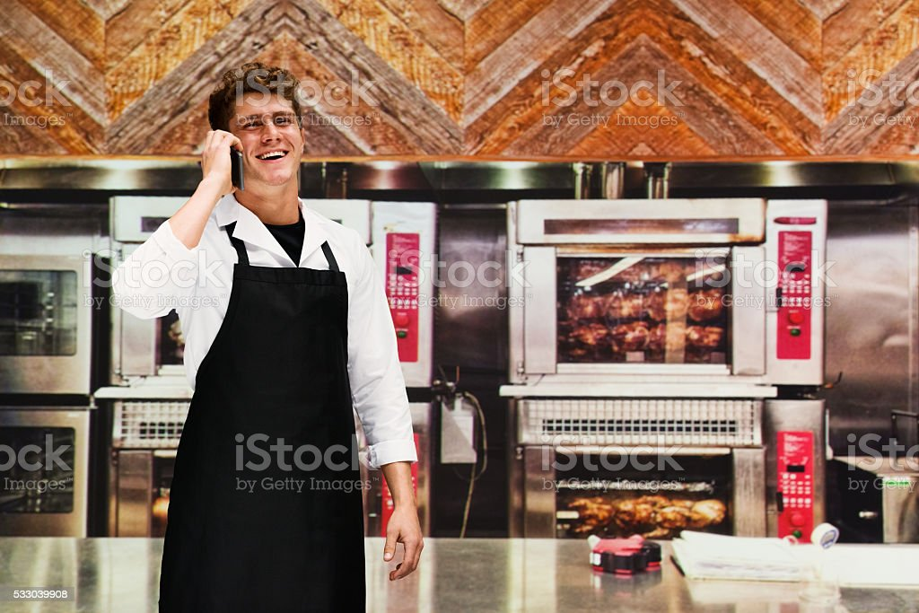 Smiling chef on phone in kitchen stock photo