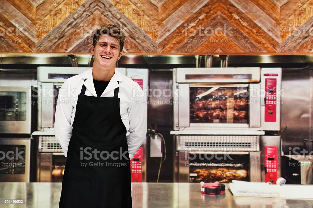 Smiling chef standing in kitchen stock photo