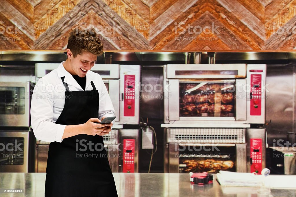 Smiling chef using phone in kitchen stock photo