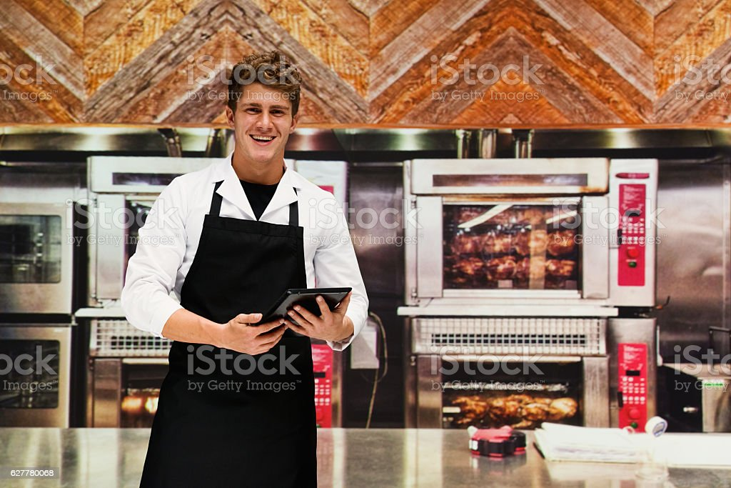 Smiling chef using tablet in kitchen stock photo