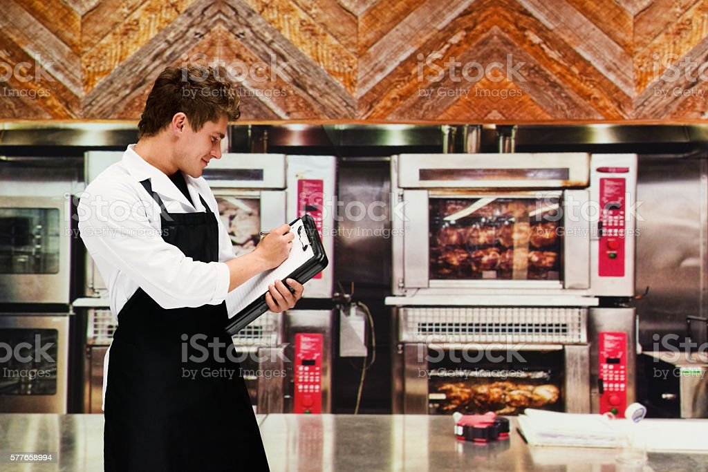 Smiling chef writing on clipboard in kitchen stock photo
