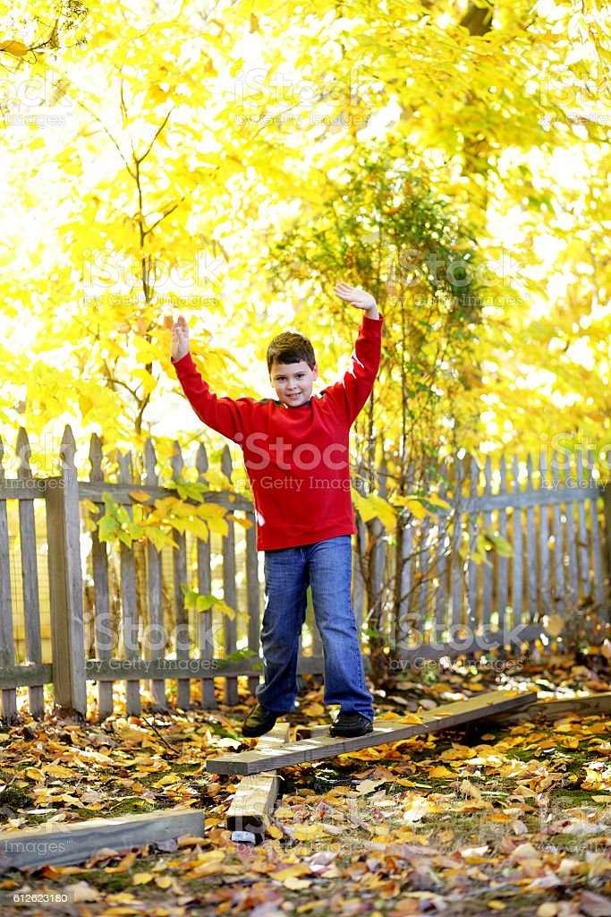 Smiling child balancing on a beam in backyard stock photo