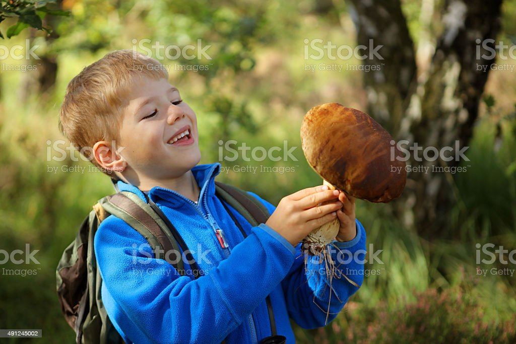 Smiling Child Holding a Big Boletus Mushroom in The Forest stock photo