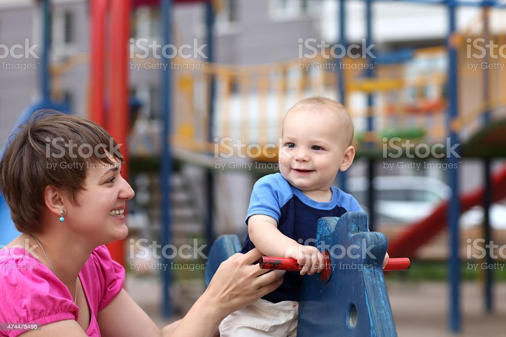 Smiling child on wooden horse stock photo