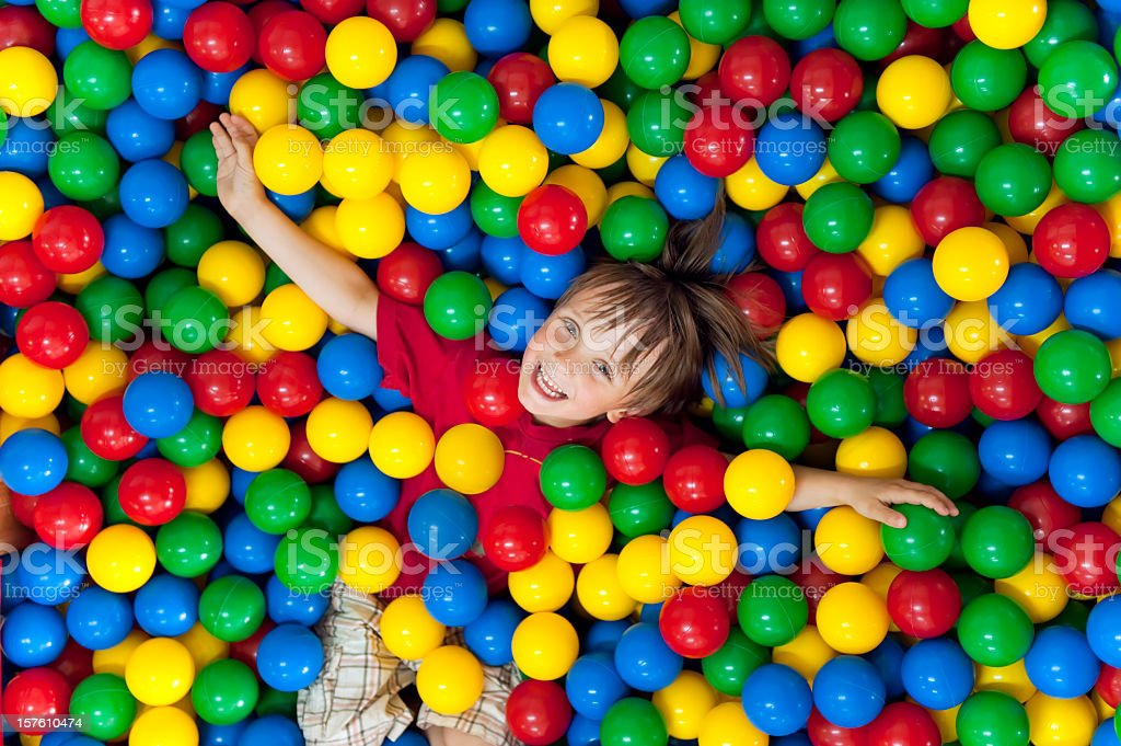 Smiling child playing in a colorful ball pit stock photo