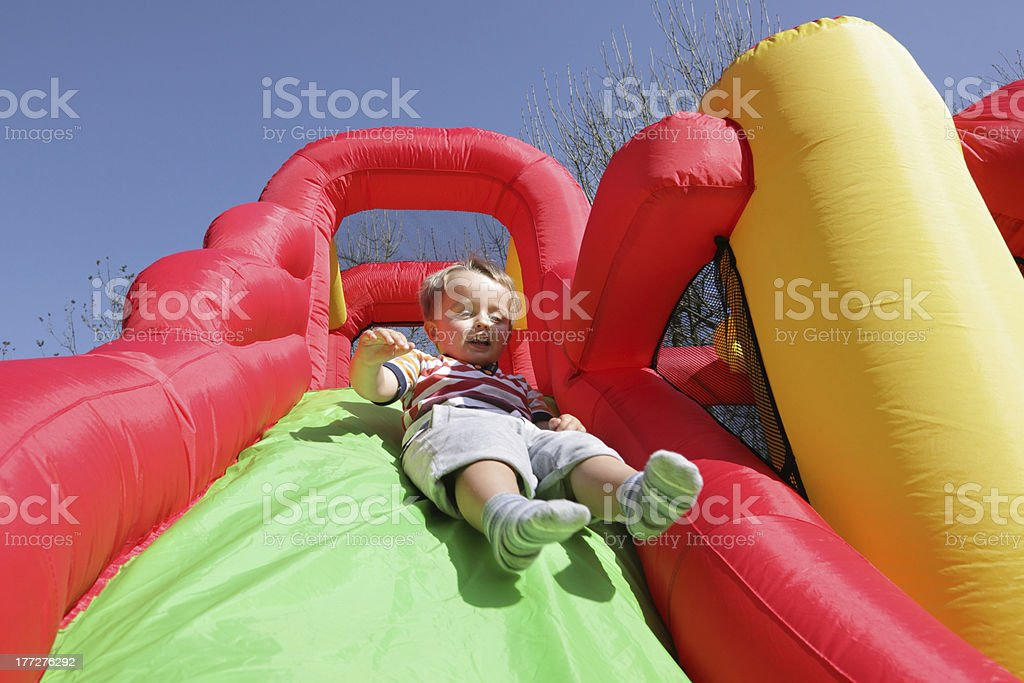 Smiling child sliding down colorful bouncy castle stock photo