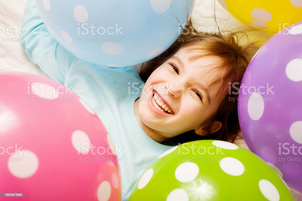 Smiling child surrounded by polka dot balloons stock photo