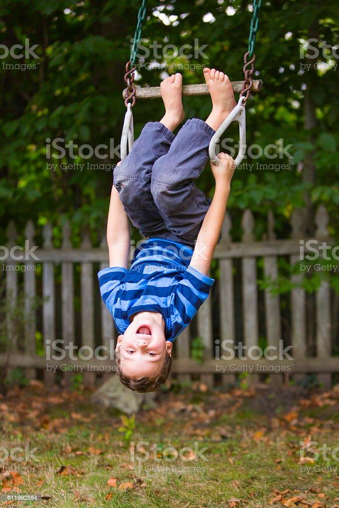 Smiling child upside down in motion on backyard swing set stock photo