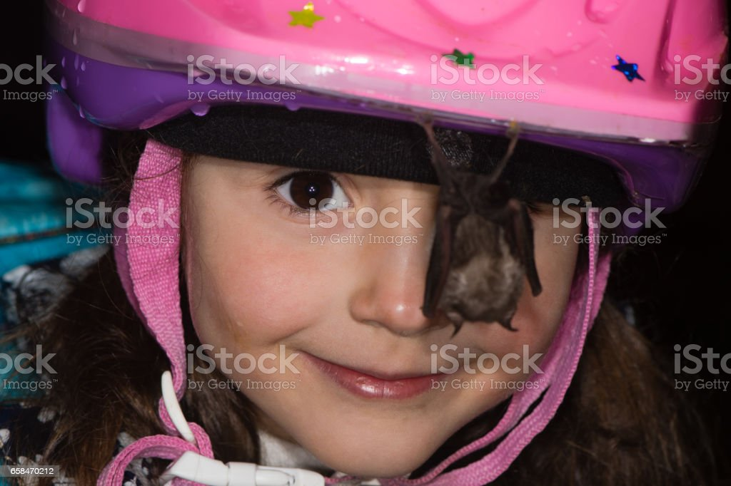 Smiling child with bat hanging from helmet stock photo