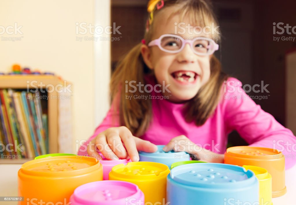 Smiling child with poor vision playing with tactile toys stock photo
