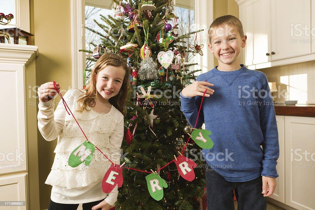 Smiling Children Celebrating in Front of Family Christmas Tree Hz stock photo