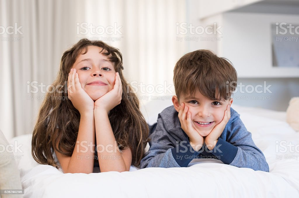 Smiling children on bed stock photo