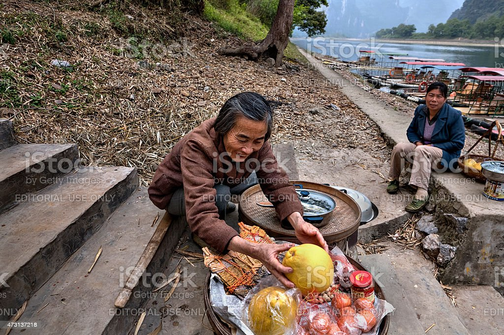Smiling Chinese woman trades fruit on steps leading to pier. stock photo