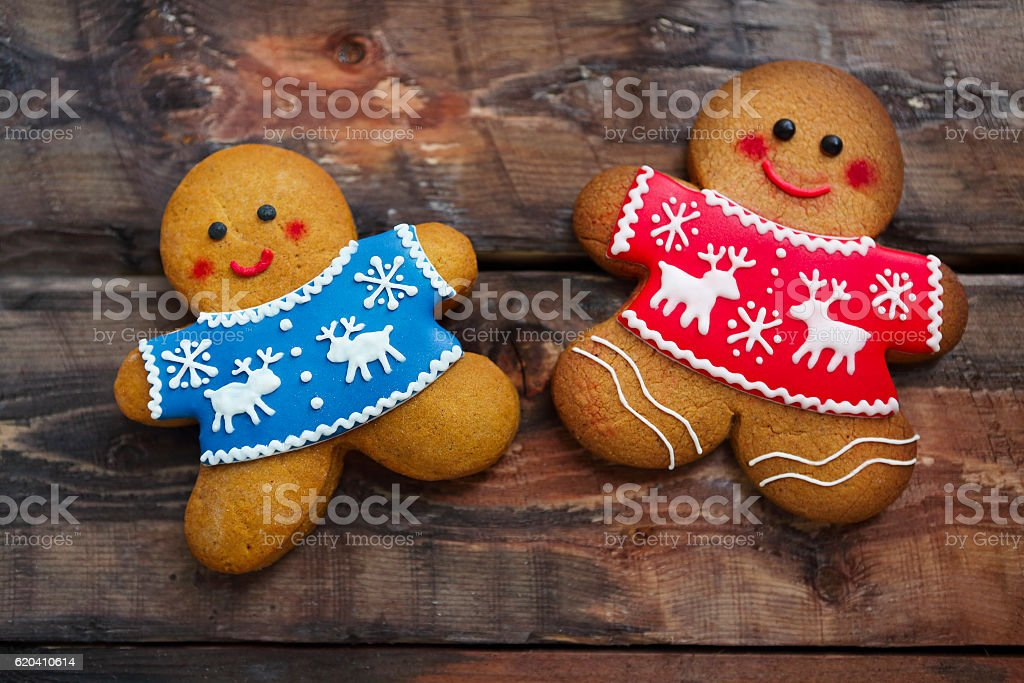 Smiling christmas gingerbread men on wooden background. stock photo