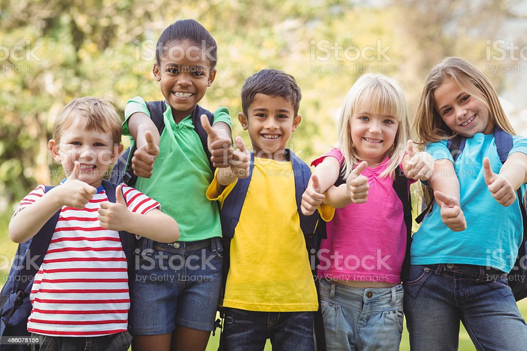 Smiling classmates doing thumbs up to camera stock photo
