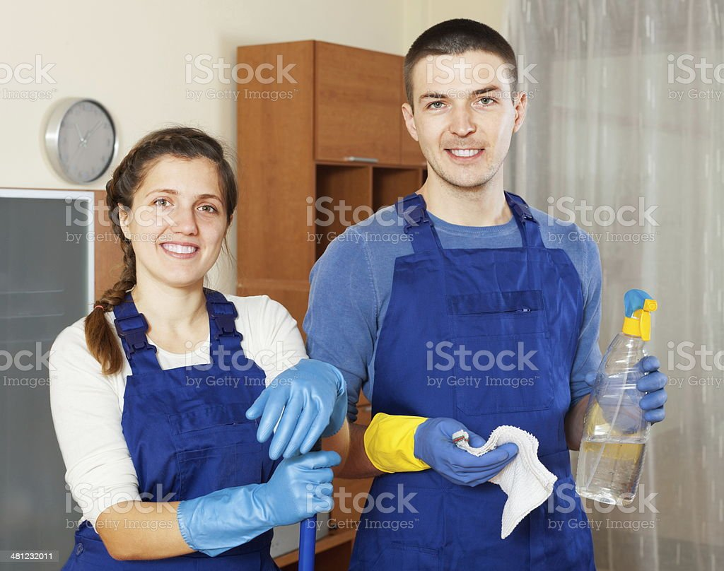 Smiling cleaners team cleaning floor stock photo