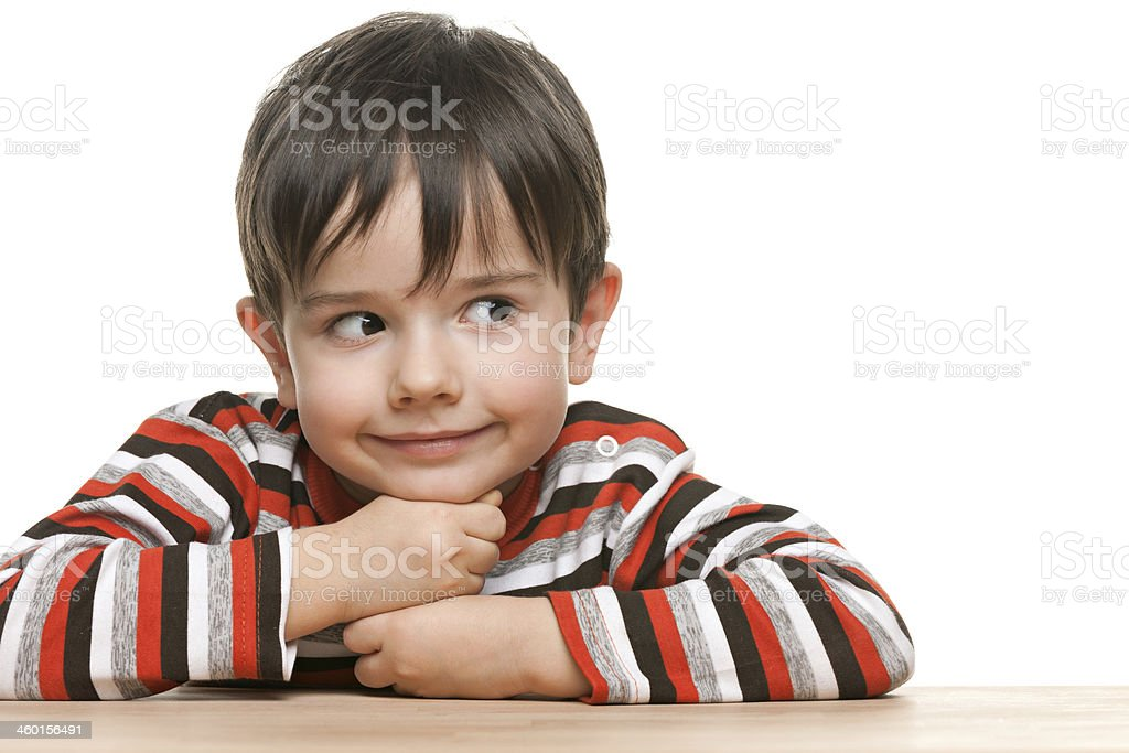 Smiling clever little boy at the desk stock photo