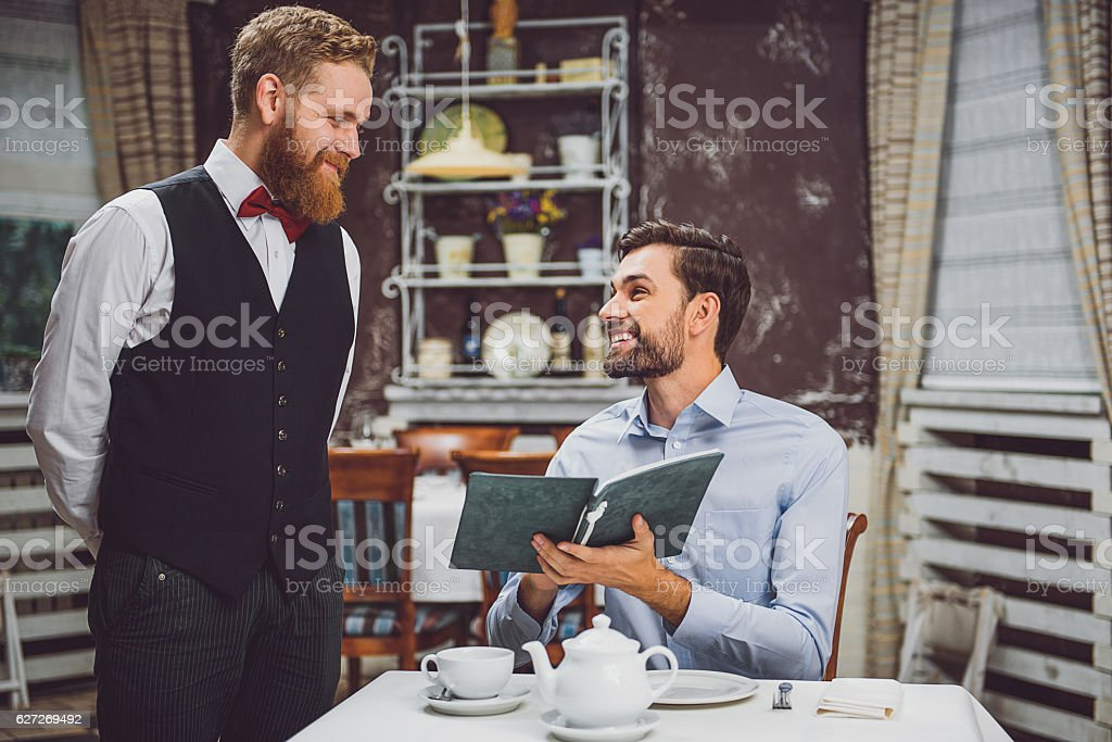 Smiling client making order in restaurant stock photo