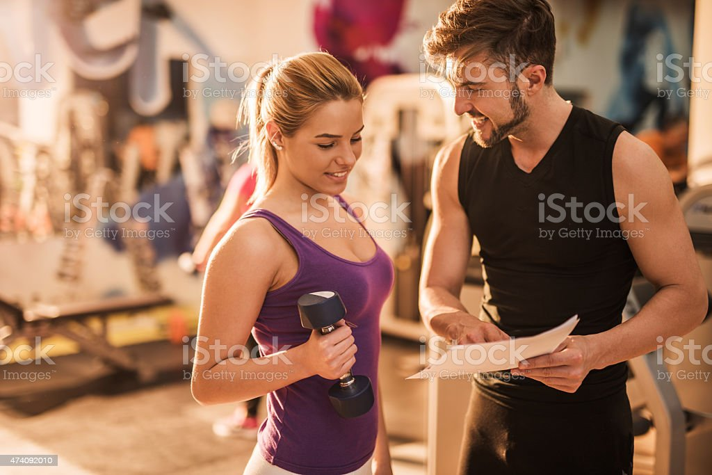 Smiling coach and young woman making a workout plan together. stock photo