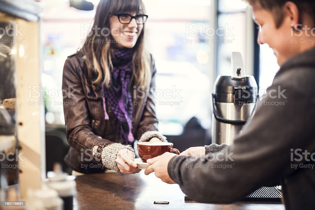 Smiling coffee shop worker hands latte to customer royalty-free stock photo