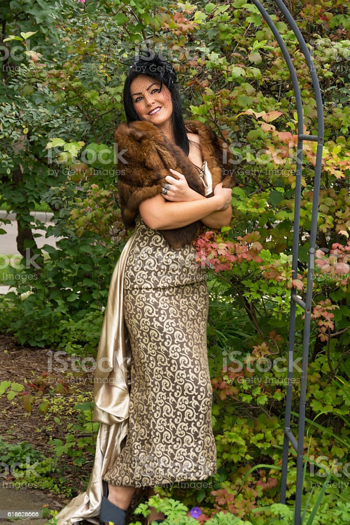 Smiling cold woman in fur stole and long dress outdoors. stock photo