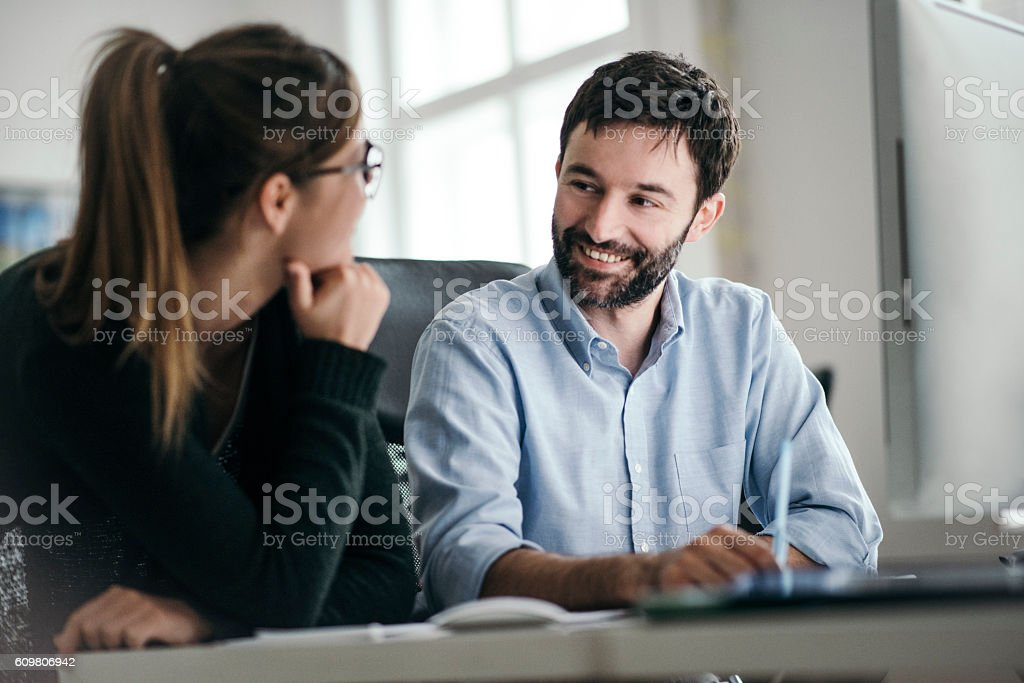 Smiling collaegues talking at office desk stock photo