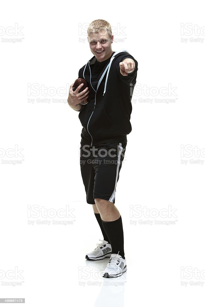 Smiling college student holding football & pointing royalty-free stock photo