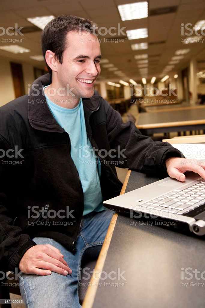 Smiling College Student using Laptop in the School Library royalty-free stock photo