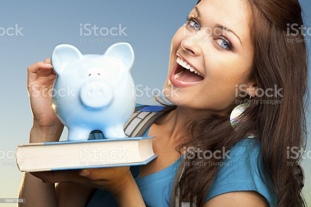 Smiling college student with blue piggy bank royalty-free stock photo