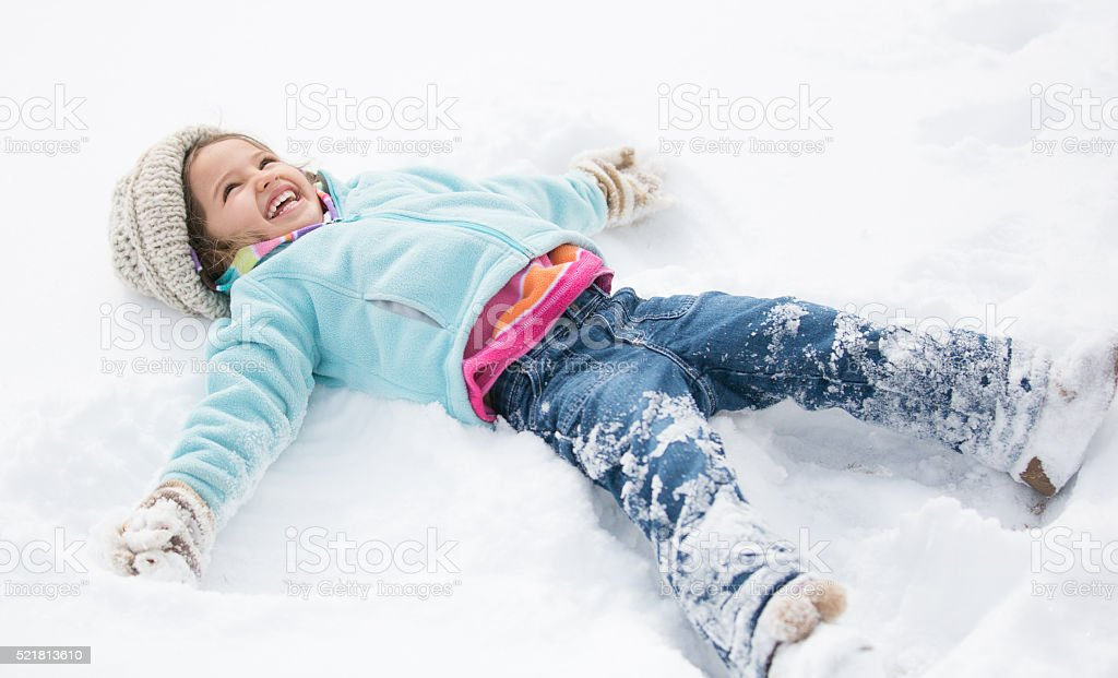 Smiling, colorful toddler makes snow angel stock photo