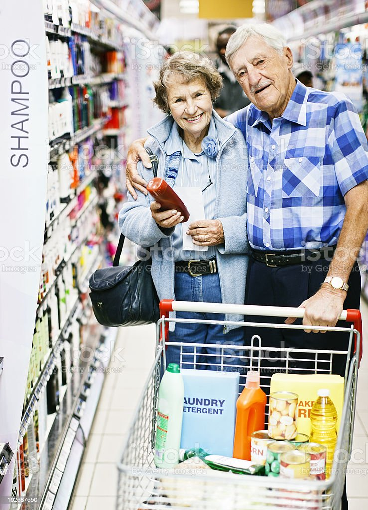 Smiling, confident, affectionate senior couple select toiletries in supermarket stock photo