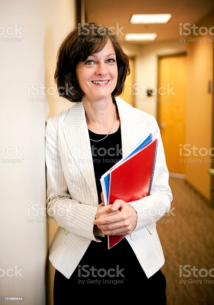 A smiling confident businesswoman holding a document royalty-free stock photo