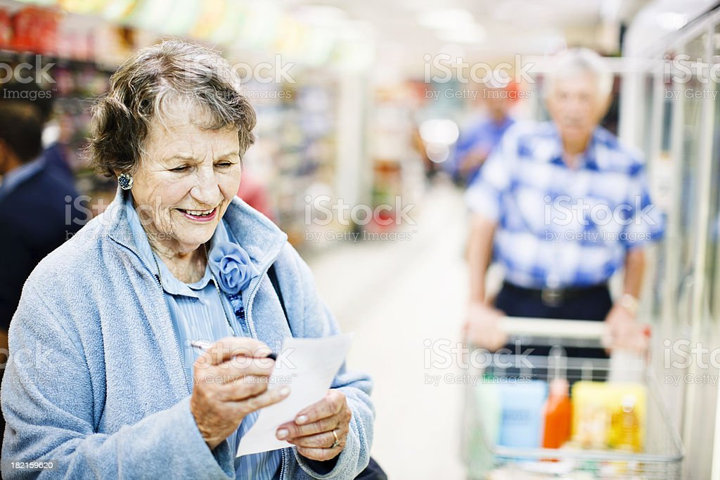 Smiling confident senior woman checks shopping list in supermarket stock photo