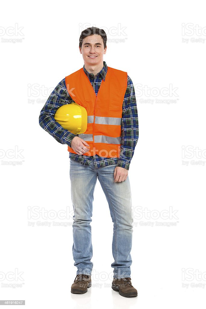 Smiling construction worker with helmet under the arm. stock photo