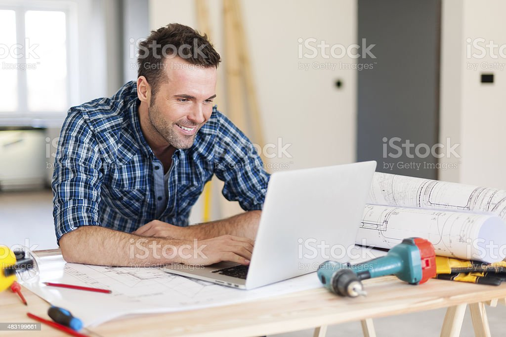 Smiling construction worker working with laptop stock photo