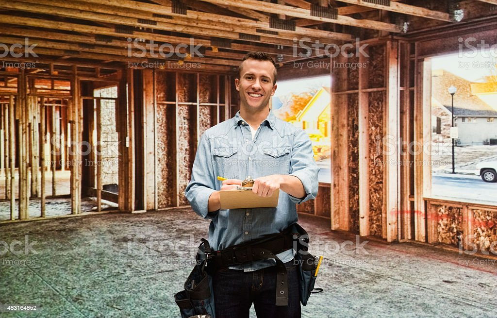 Smiling constructor worker working with clipboard stock photo