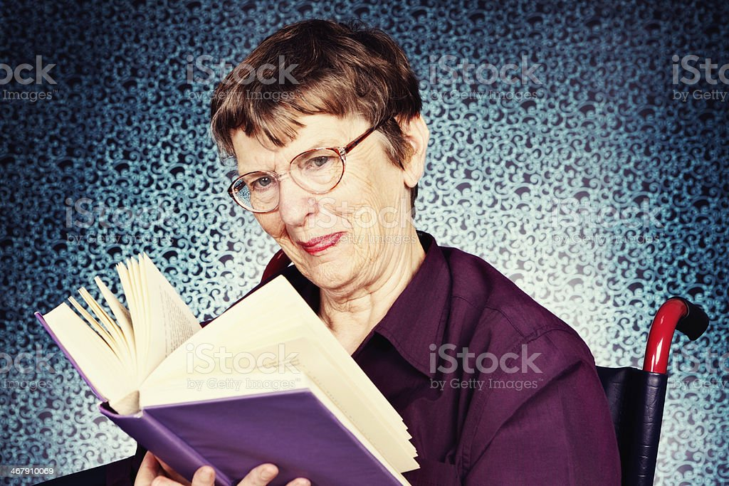 Smiling, contented  old woman looks up from book she's reading royalty-free stock photo