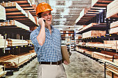 Smiling contractor at hardware and talking on phone