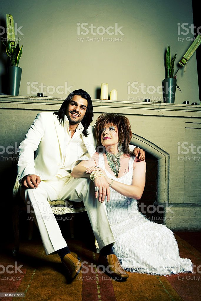 Smiling couple all in white sitting in front of fireplace. royalty-free stock photo