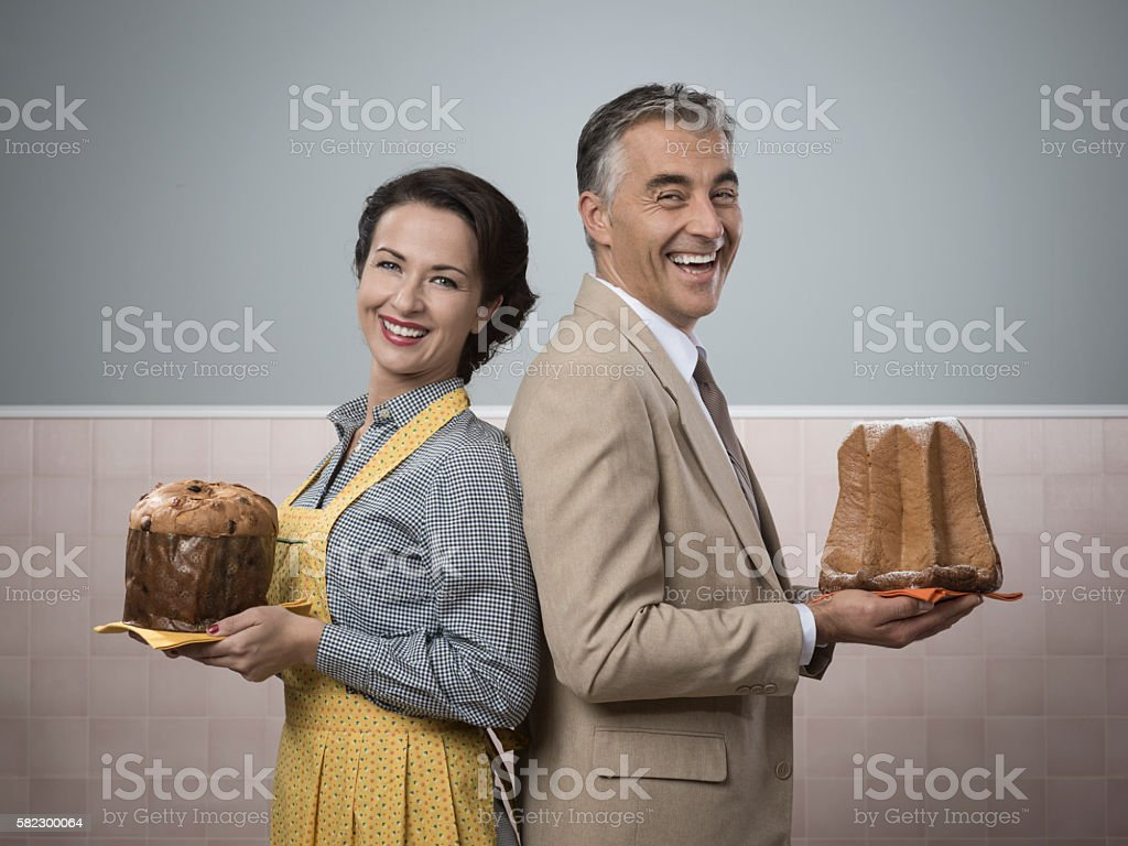 Smiling couple at home with christmas cakes stock photo