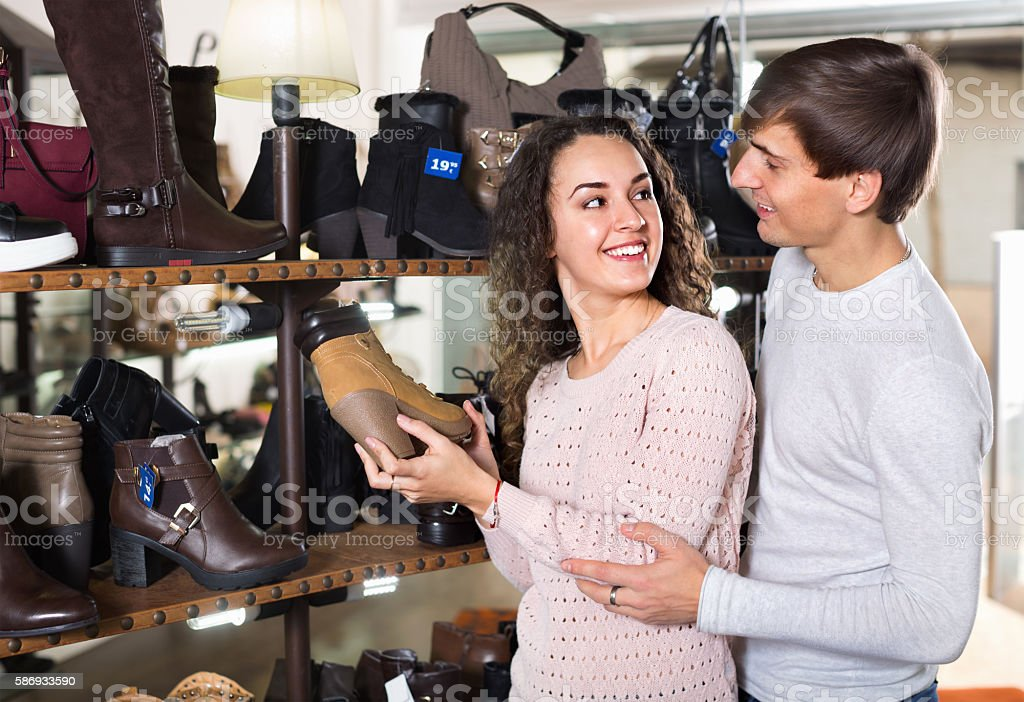 Smiling couple buying winter shoes in  store stock photo