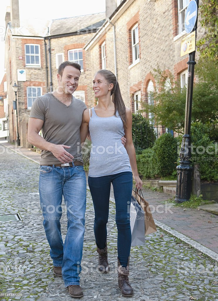 Smiling couple carrying shopping bags stock photo