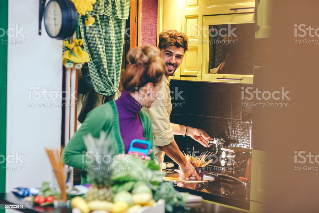 Smiling couple cooking together stock photo