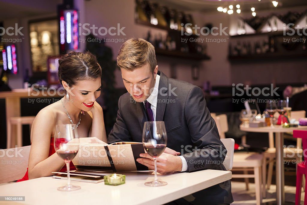 Smiling couple decide what to order stock photo