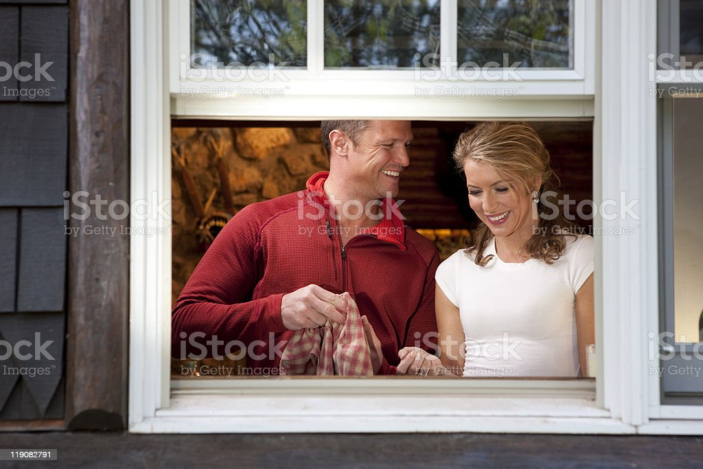 Smiling Couple Doing Dishes at Kitchen Window stock photo