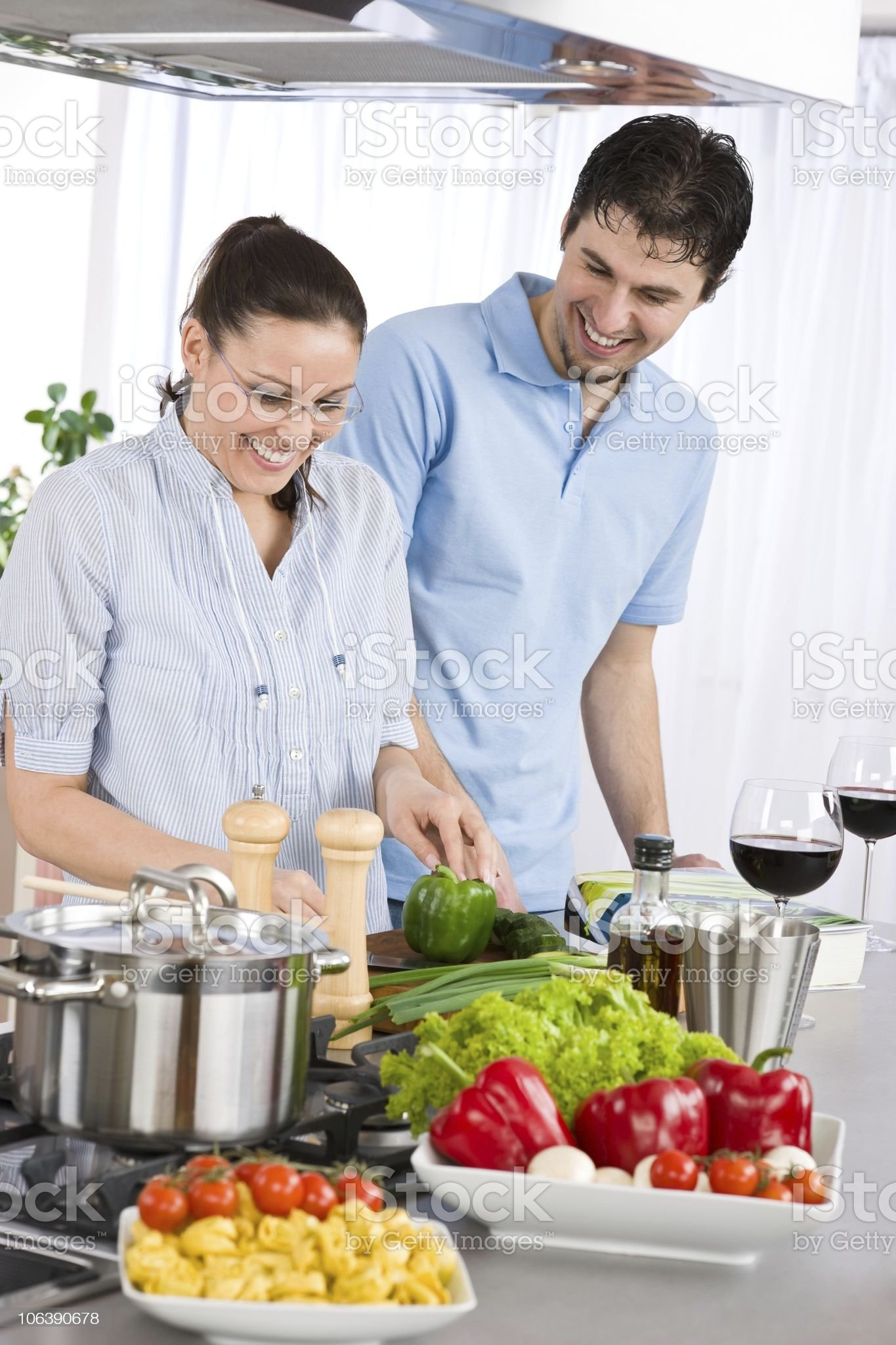 Smiling couple drink red wine cooking in modern kitchen royalty-free stock photo