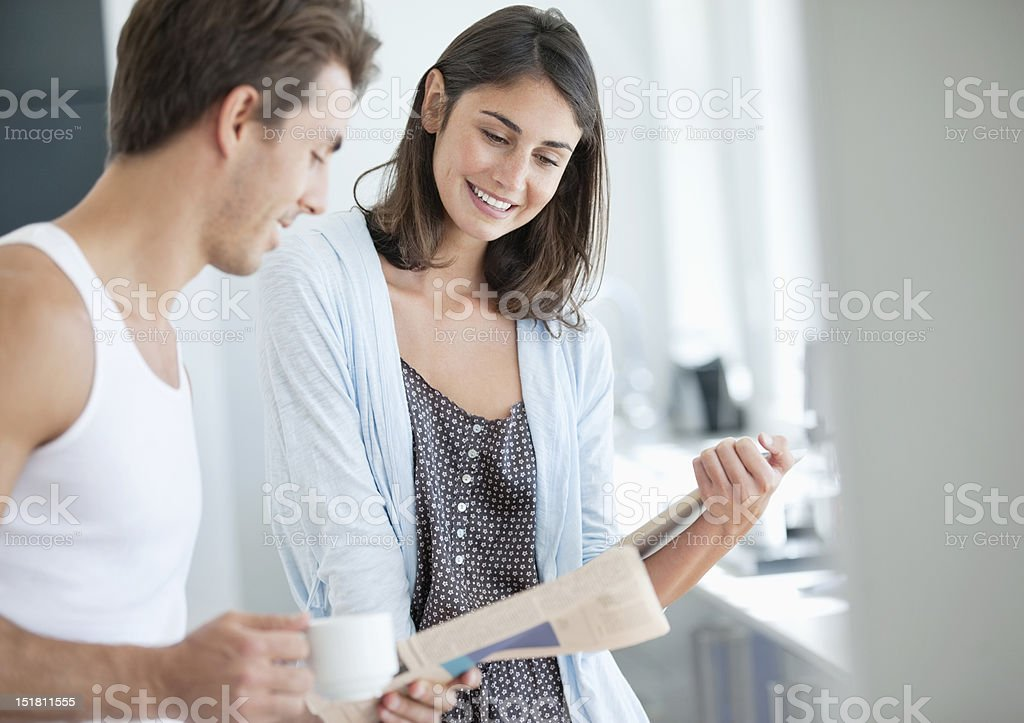 Smiling couple drinking coffee and reading newspaper royalty-free stock photo