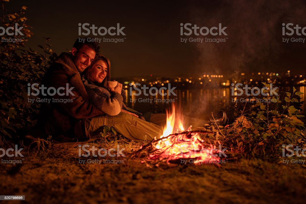 Smiling couple enjoying in campfire during the night. stock photo