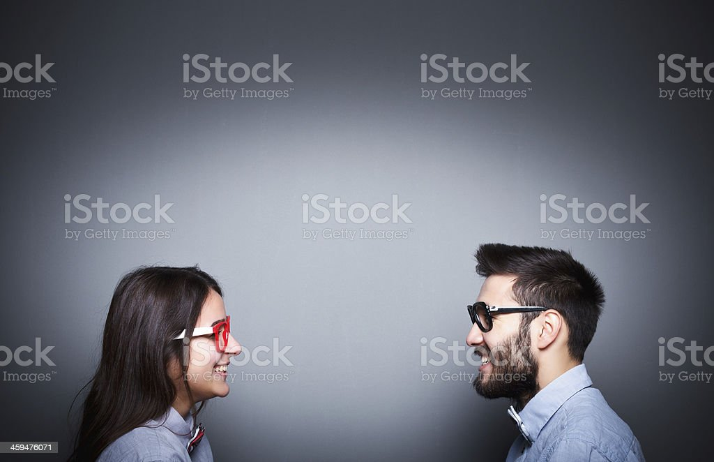Smiling couple facing each other wearing sunglasses stock photo